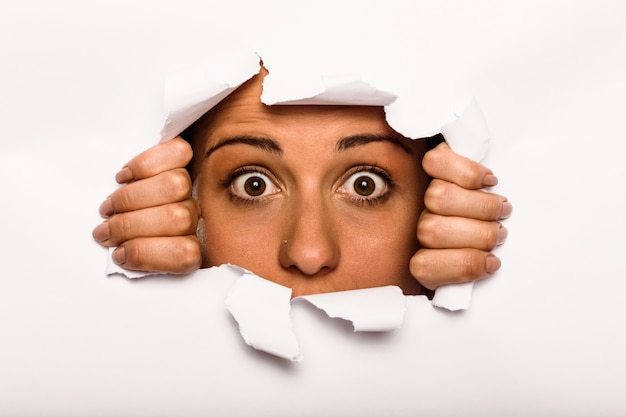 Mujer joven mirando a través de papel rasgado