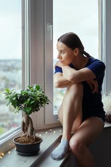 Mujer joven mirando por la ventana a la ciudad