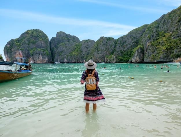 Mujer joven con mochila disfrutar en la orilla en la bahía maya, isla phi phi