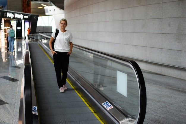 Mujer joven con una mochila en el pasillo del aeropuerto sola. concepto de viaje