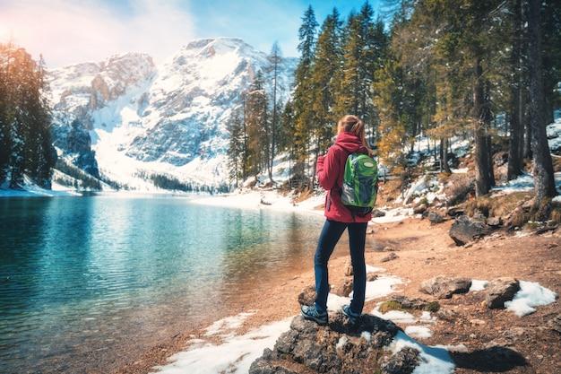 Mujer joven con mochila está de pie sobre la piedra cerca del lago con agua azul en un día soleado en otoño