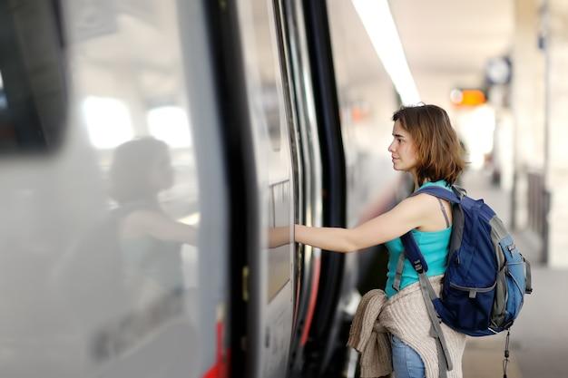 Mujer joven con mochila tomar el tren.