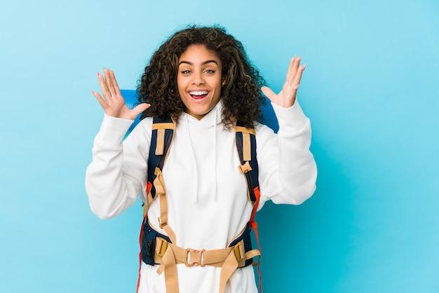 Mujer joven mochilero afroamericano que recibe una agradable sorpresa, emocionado y levantando las manos.