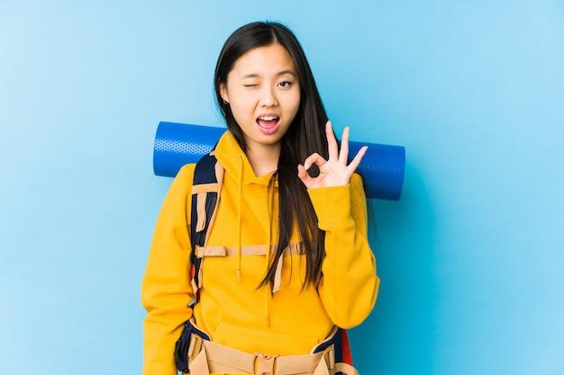 Mujer joven mochilero chino aislado guiña un ojo y tiene un gesto bien con la mano.