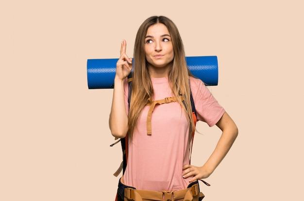 Mujer joven mochilero con los dedos cruzando y deseando lo mejor en la pared amarilla aislada
