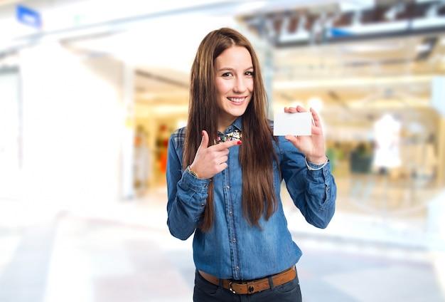 Mujer joven de moda aguantando una tarjeta blanca