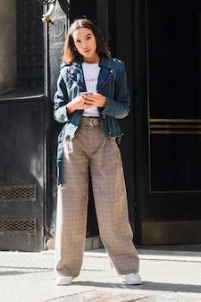 Mujer joven de moda que se coloca en la calle que sostiene el teléfono móvil disponible
