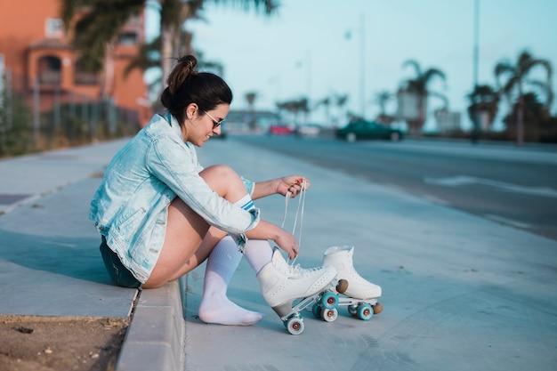 Mujer joven de moda que se sienta en la acera que ata el cordón del patín de ruedas en la calle