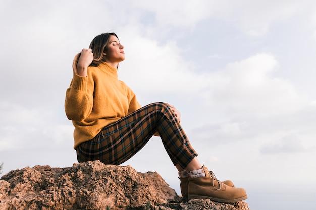 Mujer joven de moda que se sienta encima de la roca que disfruta de la naturaleza contra el cielo