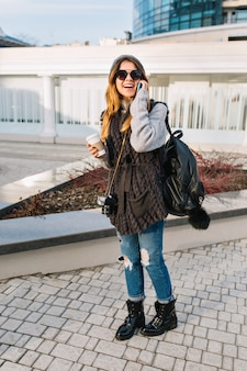 Mujer joven de moda urbana en gafas de sol frescas, suéter de invierno cálido, jeans con estilo viajando con mochila en la ciudad. estado de ánimo alegre, hablando por teléfono, café para llevar, día frío y soleado.