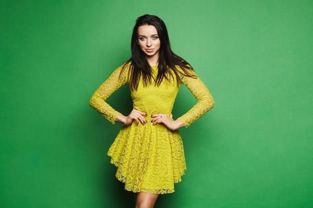 Mujer joven modelo con ojos azules y maquillaje brillante en vestido amarillo corto aislado