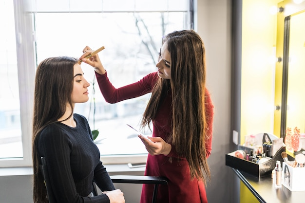 Mujer joven modelo en salón de belleza está haciendo maquillaje de noche