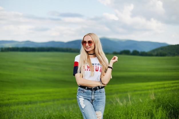 Mujer joven modelo con un traje de moda y gafas de sol rosas posando al aire libre