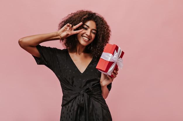 Mujer joven moderna con cabello ondulado en traje oscuro de moda guiñando un ojo, mostrando el signo de la paz, sonriendo y sosteniendo una caja de regalo roja en la pared rosa