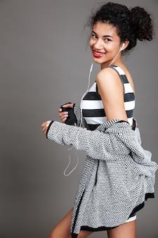 Mujer joven moderna caminando con teléfono móvil y auriculares