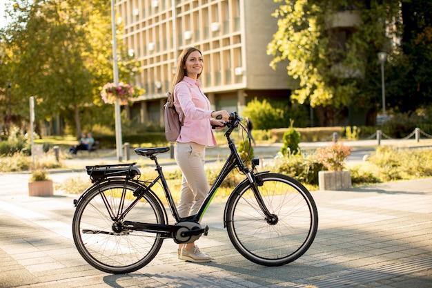 Mujer joven con moderna ciudad eléctrica e-bike limpio transporte urbano sostenible