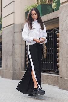 Mujer joven moderna elegante que camina en la acera en ciudad
