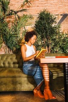 Mujer joven moderna que escribe en el diario con la pluma en el restaurante