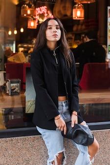 Mujer joven moderna que sostiene el casquillo en la mano que se sienta delante de restaurante de la ventana