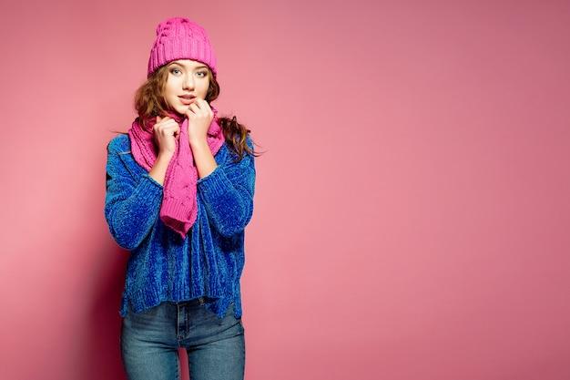 Mujer joven moderna con suéter azul y sombrero rosa, y bufanda posando, haciendo divertida expresión facial.