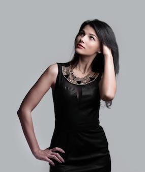 Mujer joven moderna en vestido negro. aislado sobre fondo gris