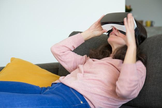 Mujer joven moderna viendo video en simulador de realidad virtual