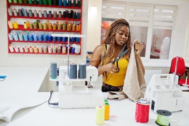 Mujer joven modista africana cose ropa en la máquina de coser y utiliza tijeras en la oficina de sastre. costurera negra mujer.