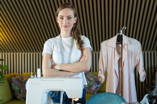 Mujer joven modista posa en un taller con los brazos cruzados contra una máquina de coser