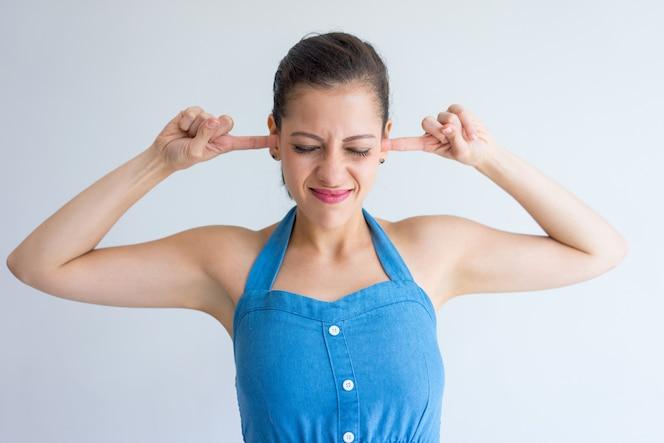 Mujer joven molesta con los ojos cerrados y cubriendo las orejas con los dedos.