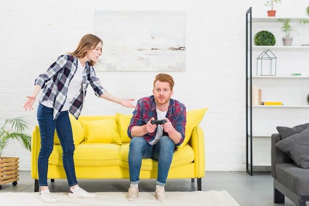 Mujer joven molesta que lucha con su novio que juega el videojuego con la palanca de mando