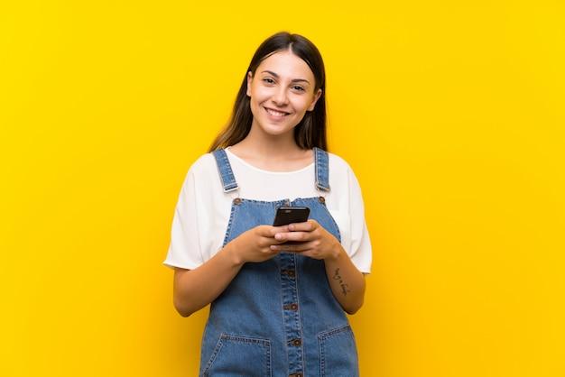 Mujer joven en mono enviando un mensaje con el móvil