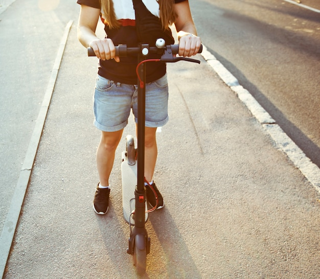Mujer joven está montando en scooter eléctrico por la ciudad de noche por caminos