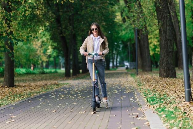 Mujer joven montando un scooter eléctrico en un parque de otoño. transporte verde, problemas de atascos.