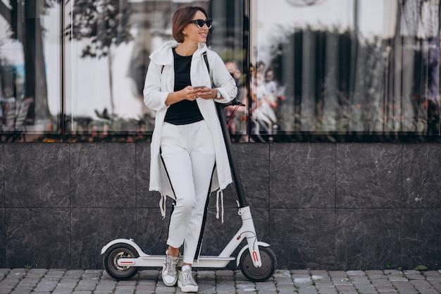 Mujer joven montando scotter en la ciudad y usando el teléfono