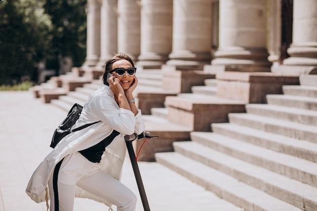 Mujer joven montando scotter por el edificio de la universidad y usando el teléfono