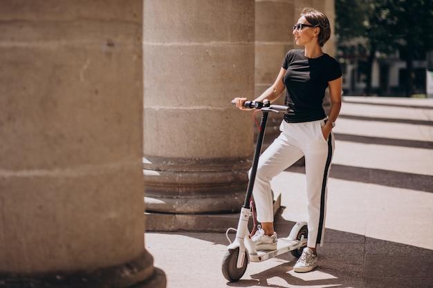 Mujer joven montando scotter por el edificio de la universidad
