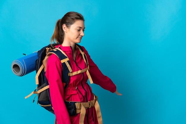 Mujer joven montañista aislada extendiendo las manos hacia el lado para invitar a venir