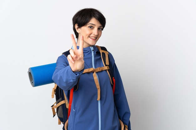Mujer joven montañista sobre aislados sonriendo y mostrando el signo de la victoria