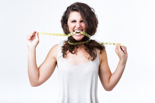Mujer joven mordiendo cinta métrica sobre fondo blanco.