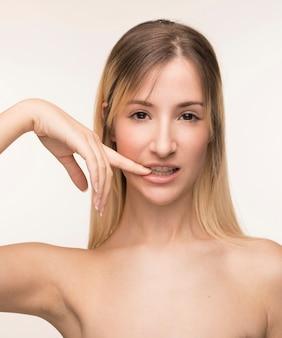 Mujer joven mordiendo su pose de uñas