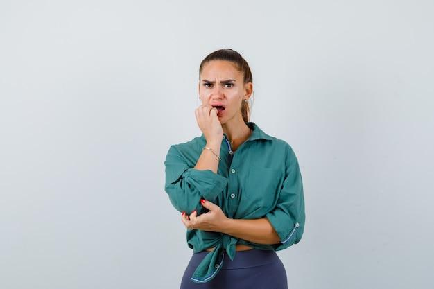 Mujer joven mordiéndose las uñas emocionalmente en camisa verde y con aspecto preocupado. vista frontal.