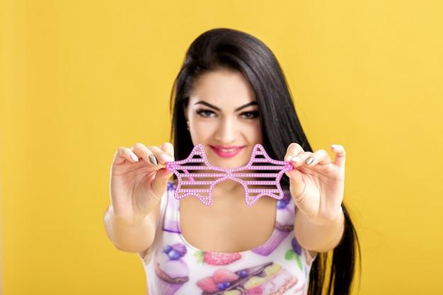 Mujer joven morena en camiseta rosa sin mangas en amarillo mujer divertida con gafas de sol rosa se centran en gafas