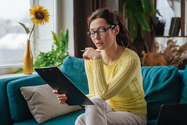 Mujer joven morena completa la información en el cuestionario haciendo una solicitud de contratación en