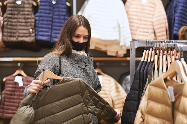 Mujer joven morena con máscara médica elige ropa en la tienda y realiza compras