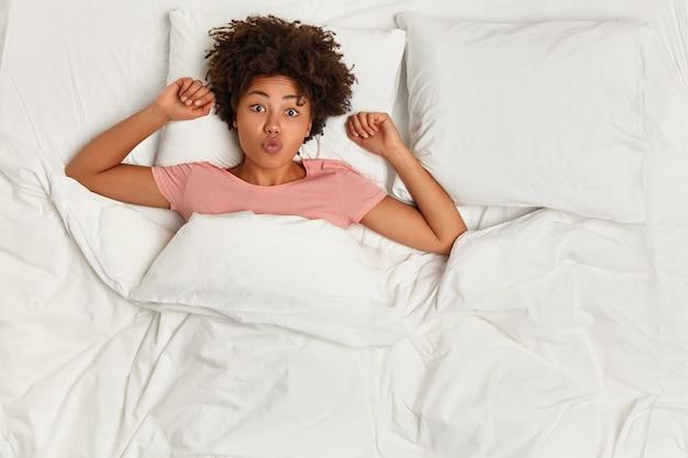 Mujer joven, morena, mentira en cama