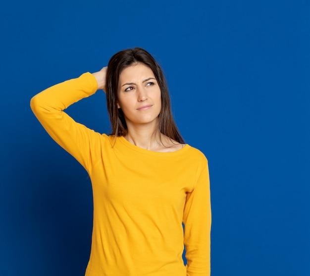 Mujer joven morena que gesticula sobre la pared azul