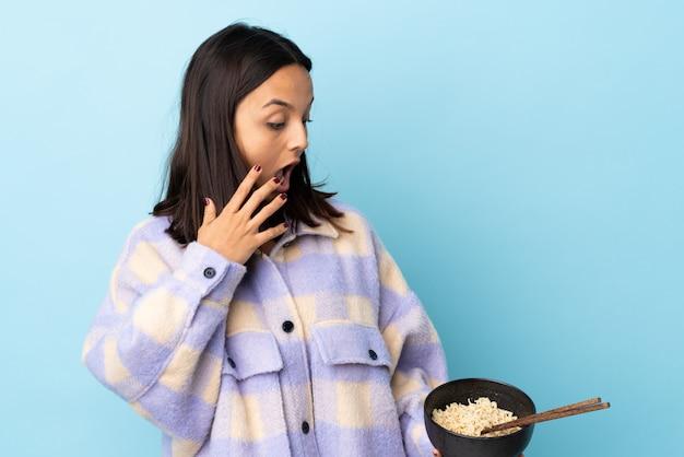 Mujer joven morena de raza mixta sobre pared azul con expresión facial sorprendida y conmocionada mientras sostiene un plato de fideos con palillos.