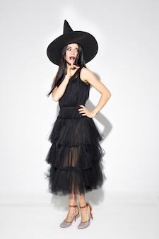 Mujer joven morena con sombrero negro y traje sobre fondo blanco. modelo femenino caucásico atractivo. halloween, viernes negro, cyber monday, ventas, concepto de otoño. copyspace. bailando, posando.