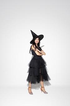 Mujer joven morena con sombrero negro y traje sobre fondo blanco. modelo femenino caucásico atractivo. halloween, viernes negro, cyber monday, ventas, concepto de otoño. copyspace. manos de pie cruzadas.
