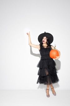Mujer joven morena con sombrero negro y traje sobre fondo blanco. modelo femenino caucásico atractivo. halloween, viernes negro, cyber monday, ventas, concepto de otoño. copyspace. sostiene la calabaza, apuntando.